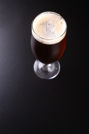 topdown: Tall tulip glass of amber ale over a dark background
