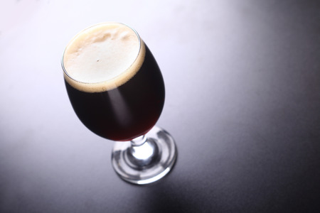 topdown: Small tulip glass full of dark beer shot topdown on a dark background