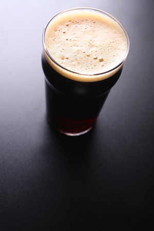 topdown: Nonic pint glass of dark ale shot topdown over a dark background
