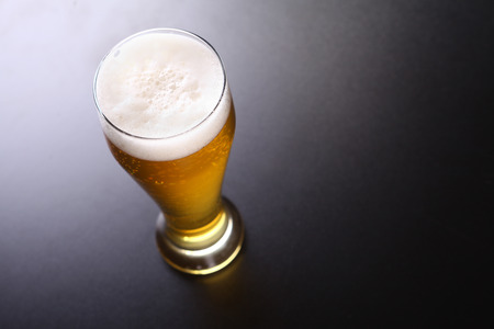 topdown: Tall glass of light lager beer shot topdown over a dark background