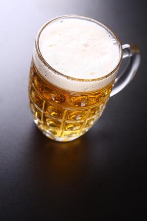 topdown: Classic glass mug full of light lager beer shot topdown over a dark background