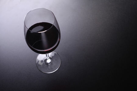 topdown: Glass of red wine over a dark background shot from above