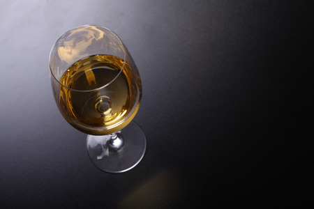 topdown: Glass full of white wine over a dark background shot from above