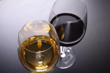 topdown: Glasses of red and white wine over a dark background shot topdown