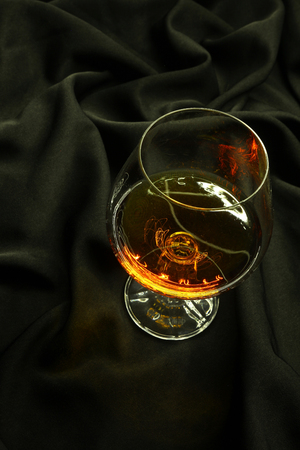 distillate: Glass of brandy standing on a crumpled black fabric