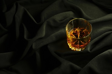 tumbler glass: Tumbler glass of whiskey standing on black crumpled fabric Stock Photo