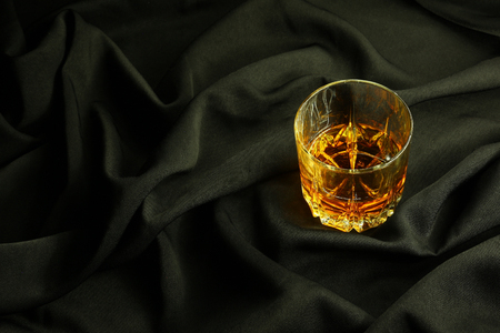 distillate: Tumbler glass of whiskey standing on black crumpled fabric Stock Photo