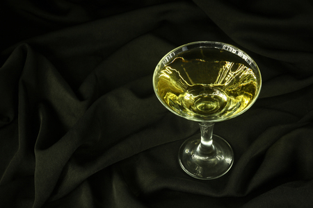 vermouth: Classic vermouth glass with drink standing on black crumpled fabric