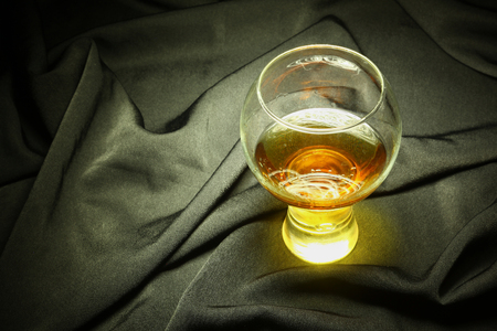 distillate: Glass of brandy standing on black crumpled fabric with light brush accent on the drink