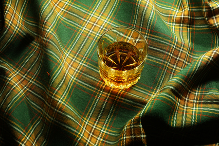 distillate: Glass of Skotch whiskey resting on a traditional tartan cloth Stock Photo