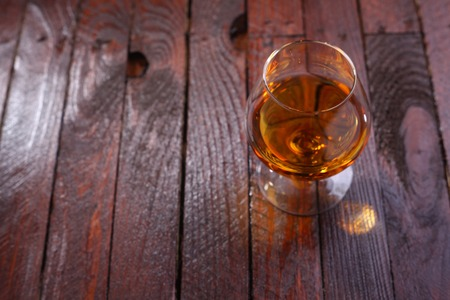 snifter: Snifter glass full of brandy standing on a wooden table