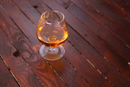 brandy: Snifter glass full of brandy standing on a wooden table