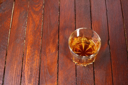 tumbler: Tumbler glass full of whisky standing on a wooden table Stock Photo