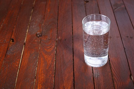 carbonated: Tall glass full of lightly carbonated drinking water standing on a wooden table