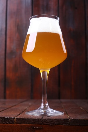 unfiltered: Glass full of unfiltered wheat beer standing on a wooden table