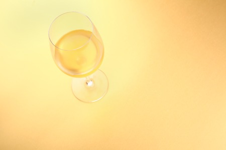 tall glass: Tall glass with white wine over a bright yellow background