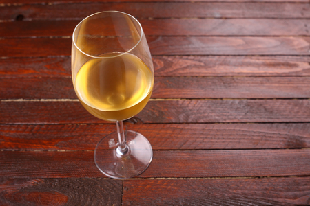 tall glass: Tall glass of white wine standing on a wooden surface Stock Photo