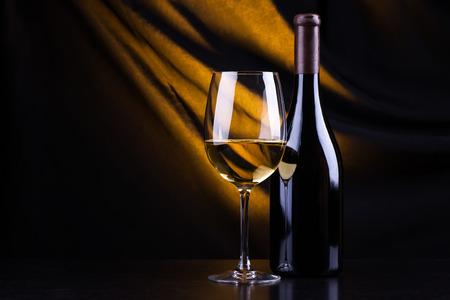 Vetro e bottiglia di vino bianco con uno sfondo scuro illuminato da una luce gialla