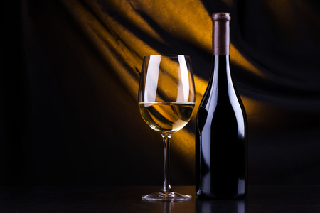 Glass and bottle of white wine with a dark background lit by a yellow light