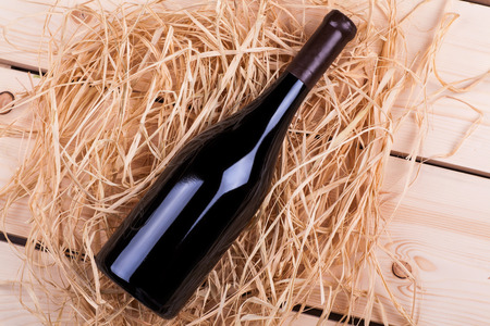 redwine: Wine bottle laying in a pile of hay over a wooden surface Stock Photo