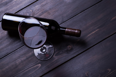redwine: Bottle and glass of red wine on a textured dark wood surface