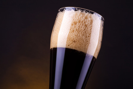 tall glass: Tall glass full of dark beer over a dark background