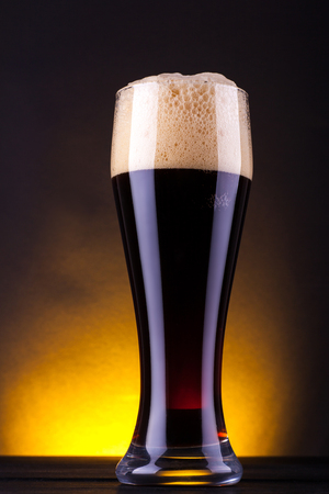 Tall glass full of dark beer over a dark background