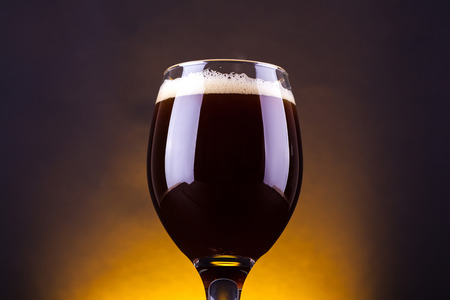 Glass full of dark brown ale beer over a dark background