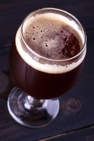 ale: Glass full of dark brown ale beer over a dark background