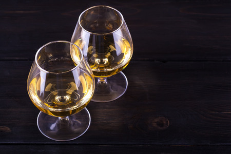 snifter: Two snifter glasses with brandy on a textured dark wood table Stock Photo