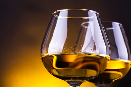 snifter: Two snifter glasses with brandy over a yellow lit background