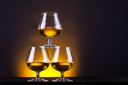 snifter: Three snifter glasses with brandy stacked into a pyramid over a yellow lit background