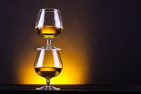 snifter: Snifter glasses with brandy stacked on top of each other over a yellow lit background