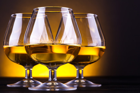 Three snifter glasses with brandy standing on a wood table over a yellow lit background Stock Photo
