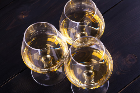 snifter: Three snifter glasses with brandy standing on a textured dark wood table