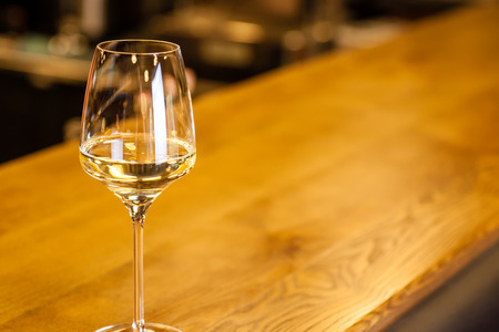 Glass of white wine standing on a bar counter in a fancy wine restaurant