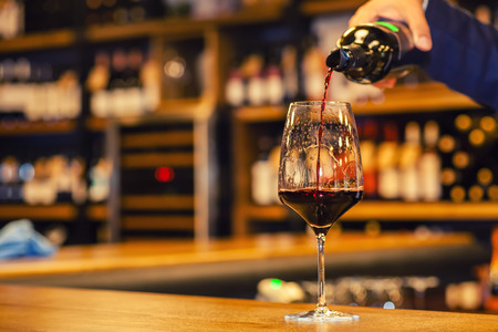 ambiance: Red wine being poured from a bottle into a glass standing on a bar counter in a restaurant
