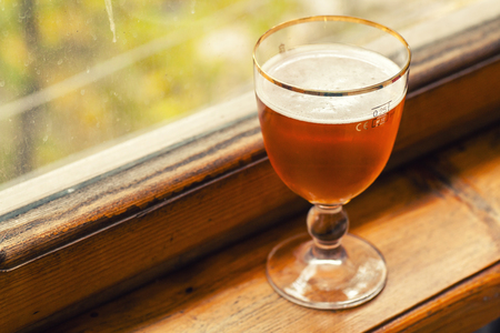 snifter: Strong ale in a special glass on a wood windowsill