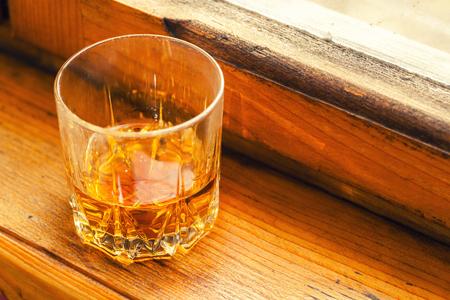 vaso de precipitado: Whisky en un vaso bajo el alféizar de una ventana de madera