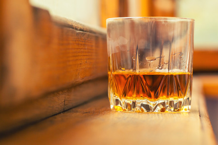 Whiskey in a tumbler glass on a wood windowsill Stock Photo