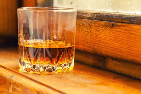 tumbler: Whiskey in a tumbler glass on a wood windowsill Stock Photo