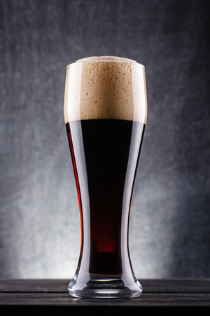 Tall glass of dark beer over a dark textured wooden background Stock Photo