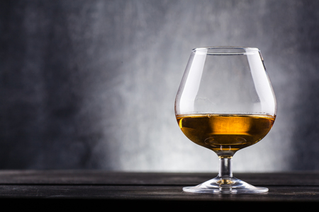 Glass of brandy over a dark textured wooden background