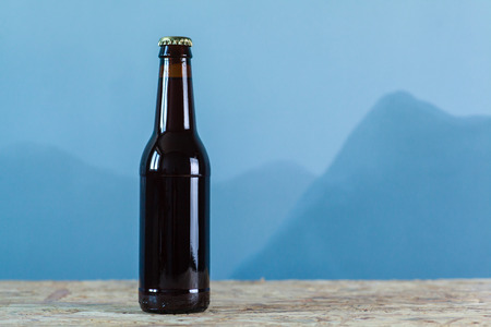 no label: Beer bottle with no label on a wooden surface over an abstract blue background