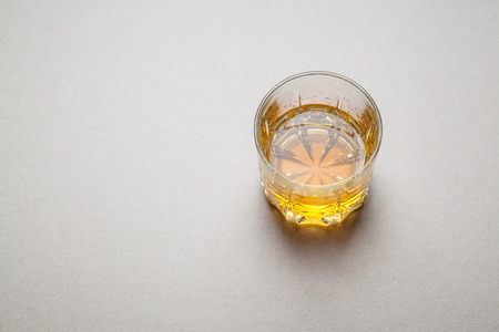 tumbler: Tumbler glass with whiskey on a gray surface Stock Photo