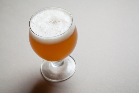 Small glass full of wheat beer on a gray table Stock Photo