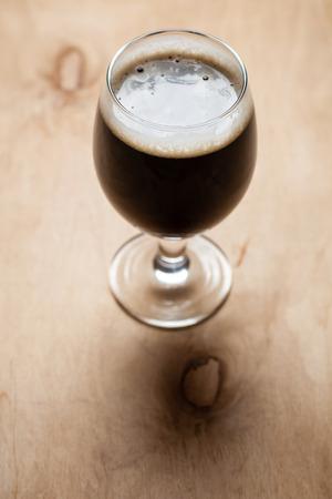 stout: Vaso lleno de cerveza negra oscura sobre una mesa de madera con textura Foto de archivo