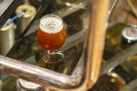 Glass full of amber ale beer standing on steps of an operating brewhouse at a brewery Stock Photo