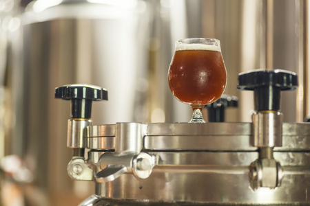 Glass full of amber ale beer standing on equipment at a brewery Stock Photo