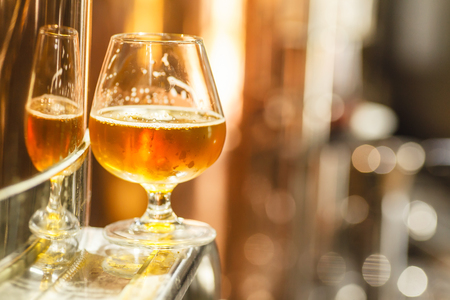 Glass with amber ale beer standing on a metal doorway of a copper lauter tun at a brewery